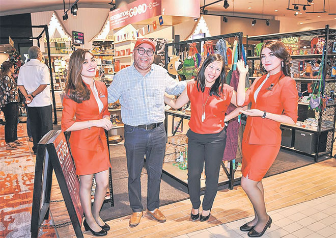 AirAsia X CEO Datuk Kamarudin Meranun (second left) posing with Yap (second right) and two staff after the launch of Destination: GOOD pop-up shop at klia2.