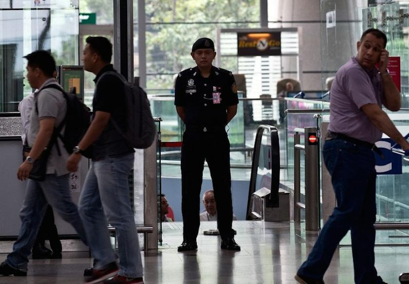 An auxiliary policeman at the KLIA departure hall was seen checking thoroughly passengers� documents and flight details before allowing them to proceed to the Immigration counters. � AFP pic