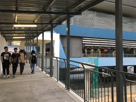 Commuters using the pedestrian link leading to the station