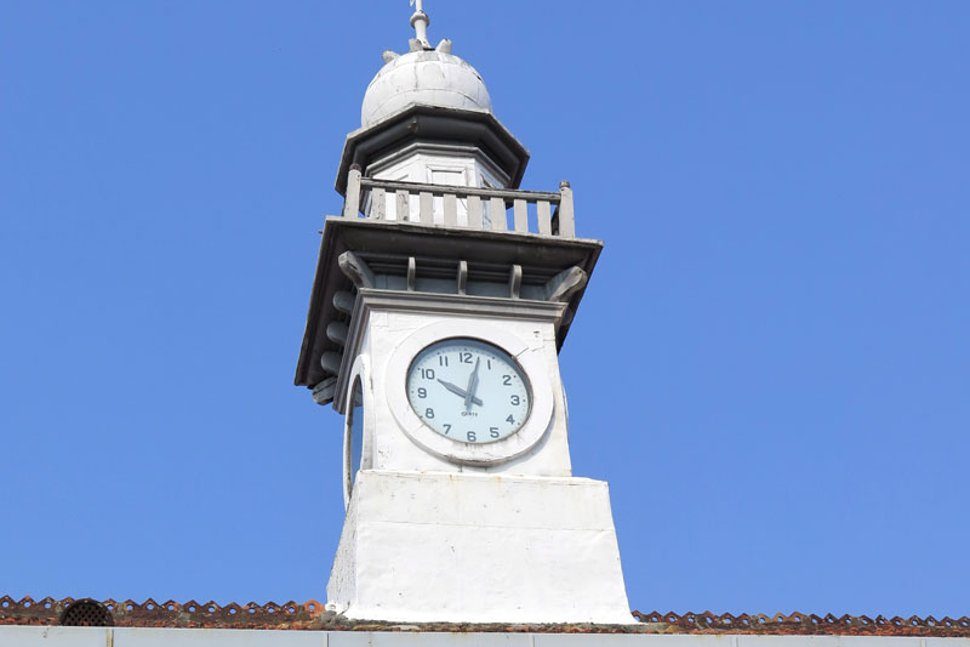 A white clock tower is erected atop the roof