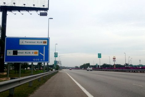 After the KLIA toll plaza, signboard and Petronas station in view