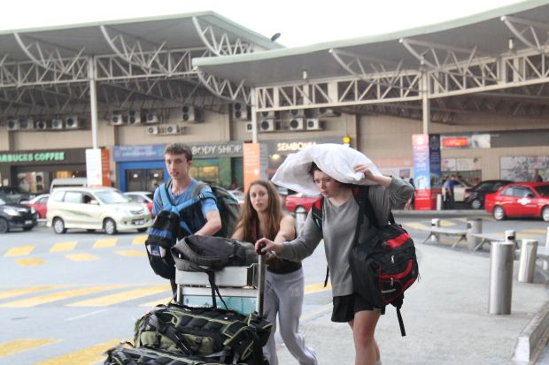 Out in the open: Foreign tourists running for shelter after getting caught in the rain at LCCT, where there's no covered walkway. Many people have become sick with the lack of quality facilities at the terminal.