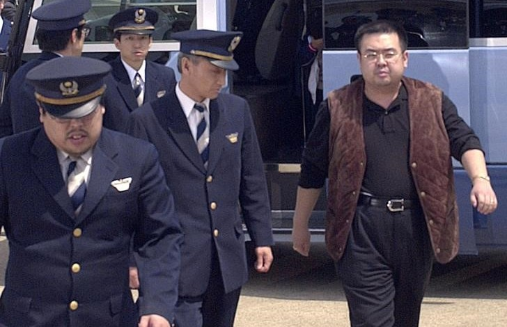 A man (R) believed to be North Korean heir-apparent Kim Jong Nam, is escorted by police as he boards a plane upon his deportation from Japan at Tokyo's Narita international airport in Narita, Japan, in this photo taken by Kyodo May 4, 2001. Picture taken May 4, 2001. Mandatory credit Kyodo/via REUTERS/Files
