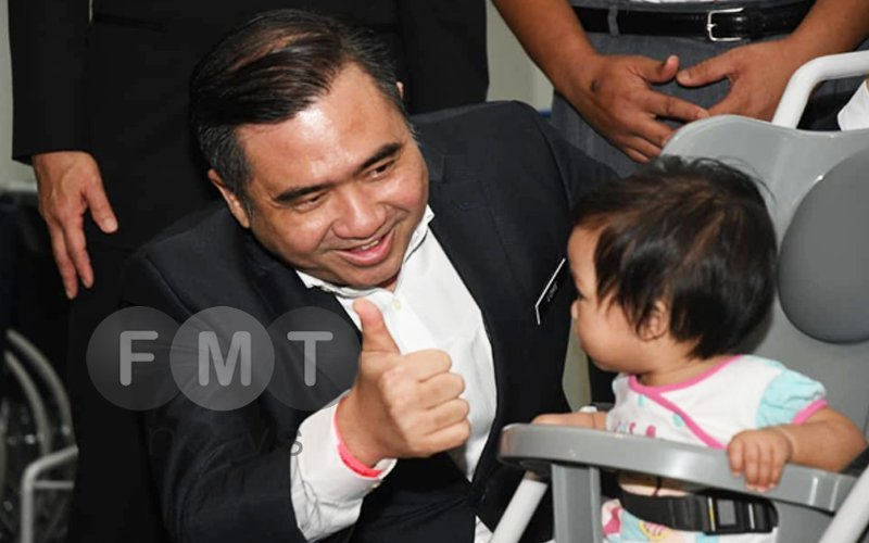 Transport Minister Loke Siew Fook gives a toddler the thumbs up at the launch of the new wheelchairs and strollers for passengers.