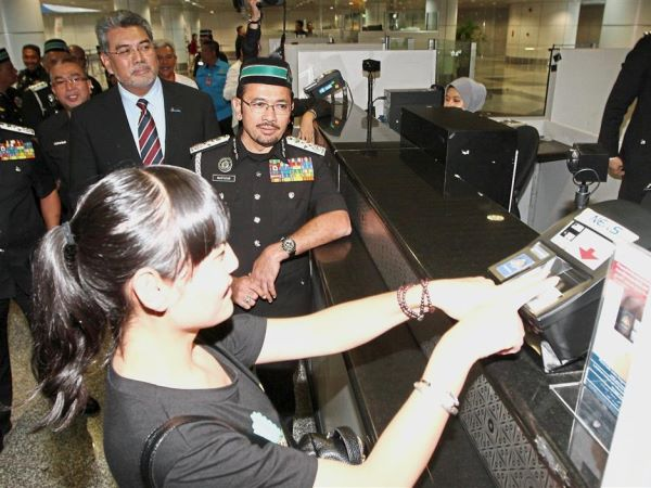Easy process: Mustafar (in uniform) checking out the immigration process at KLIA as MAHB managing director Datuk Badlisham Ghazali ?looks on.