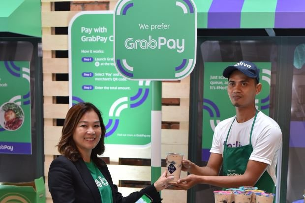 Ooi trying out the GrabPay mobile e-wallet with one of its partner merchants. - Grab