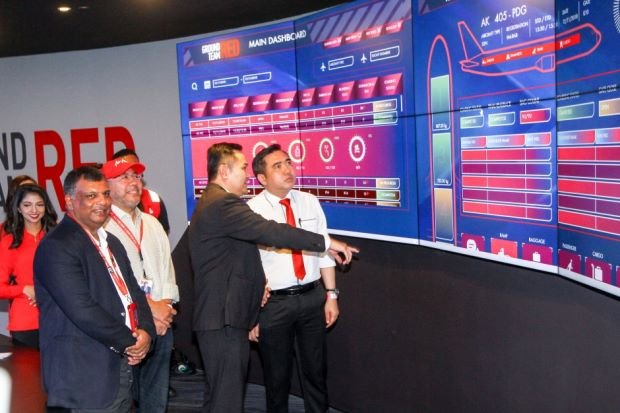 Fernandes (second from left), Kamarudin (centre) and Loke (far right) are given a tour of the Ground Team Red control centre.