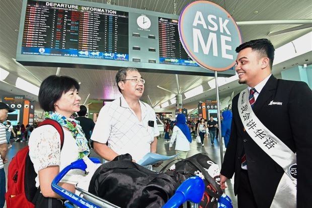 Ready to assist: A MAHB officer attending to enquiries from a couple from Hong Kong at klia2