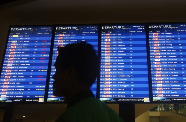 File picture of a man walking in front of a flight board at klia2 in Sepang April 30, 2014. - Reuters pic