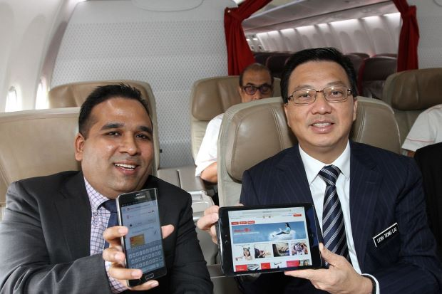 SURF IN THE AIR: Liow (right) and Chandran trying out Malindo Air's new in-flight connectivity services on board a plane during the launch of the services and the airline's in-flight magazine at klia2, Sepang.