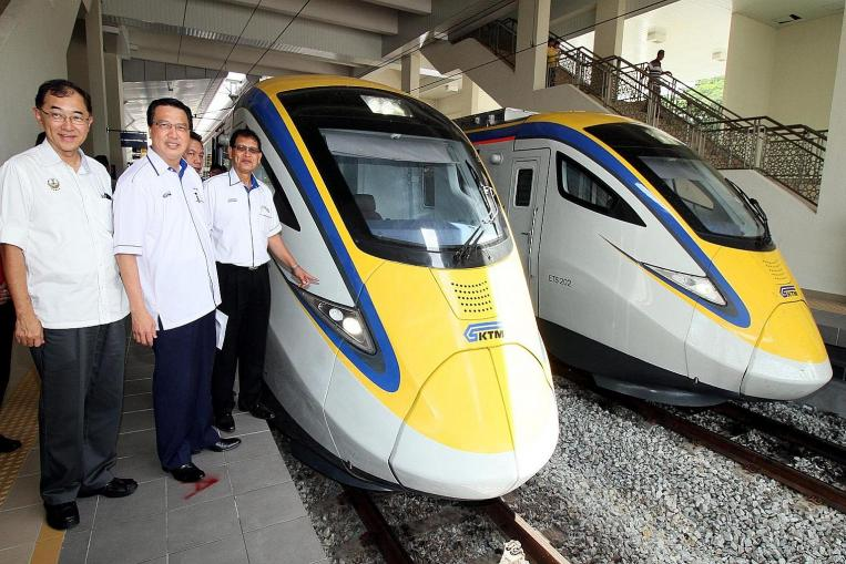 Council member Mah Hang Soon and Malaysian Transport Minister Liow Tiong Lai join KTM president Sarbini Tijan as he checks out the new electric trains.