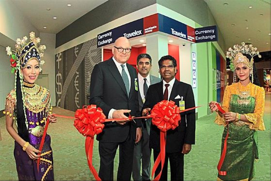 Travelex group chairman, Lloyd Dorfman and Travelex Malaysia Chairman, Tan Sri AP Arumugam, cutting the opening ceremony ribbon for Travelex, the foreign currency exchange in klia2. Looking on is Rakesh Aravind (middle) Travelex country manager for Malaysia.