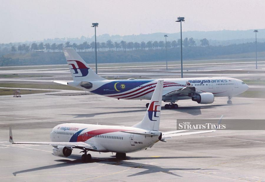 Malaysia Airlines aircraft taxiing near the runway of Kuala Lumpur International Airport.