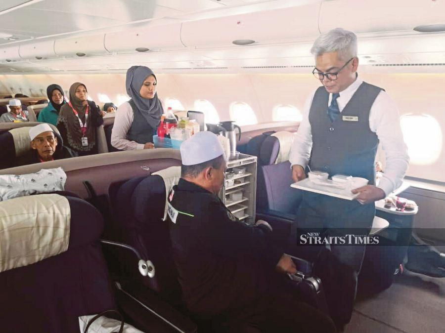 The crew of Malaysia Airlines' Project Amal serving pilgrims on a haj flight. Stiff competition from regional peers and Gulf carriers have hit the local aviation sector.