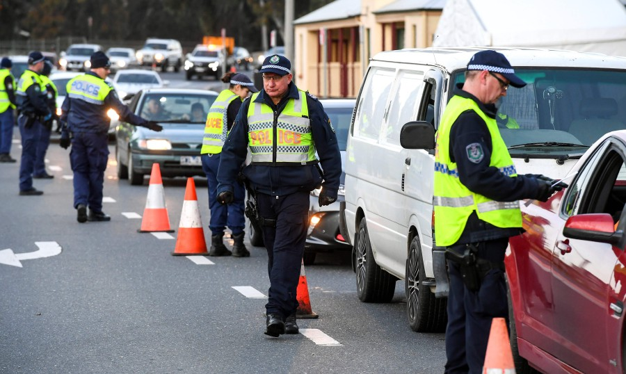 Police in the southern New South Wales (NSW) border city of Albury check cars crossing the state border from Victoria on July 8, 2020 after authorities closed the border due to an outbreak of COVID-19 coronavirus in Victoria. - AFP pic