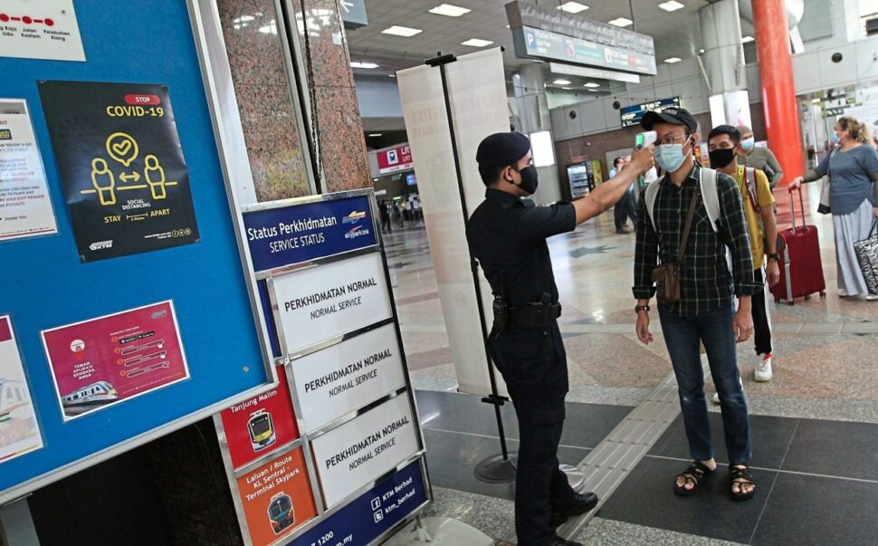 Transport checkpoint: KTMB auxiliary police personnel taking the temperature readings of ETS passengers at KL Sentral, Kuala Lumpur.