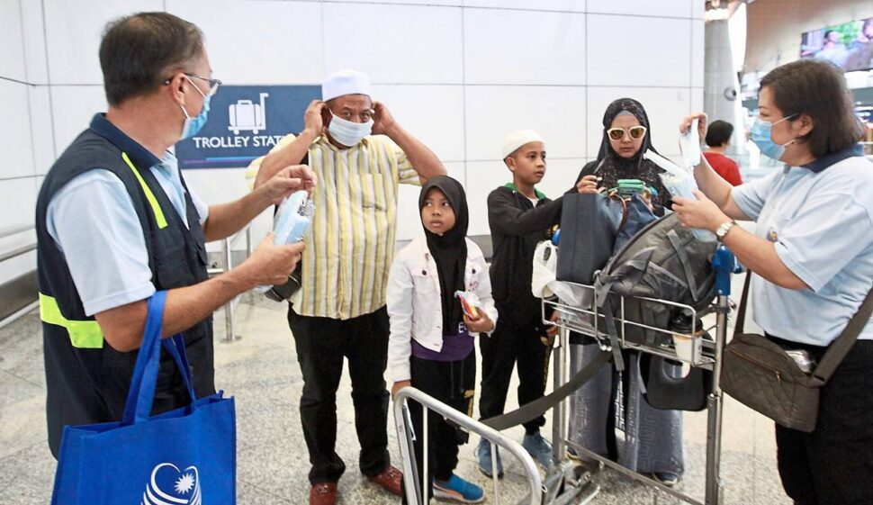 Precautionary measure: Ch'ng (left) distributing face masks to travellers and staff at KLIA.