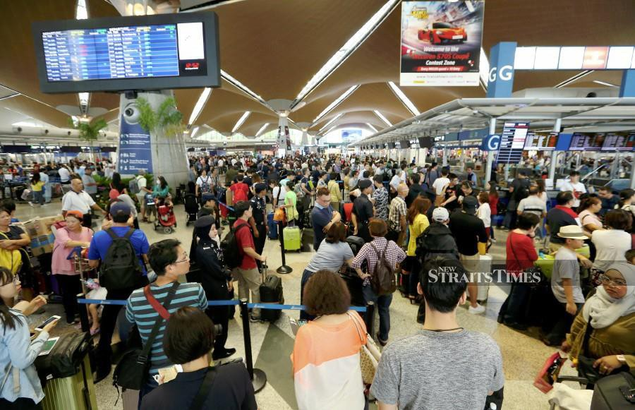 Passengers seen lining up at Kuala Lumpur International Airport following the glitch at the airport. - NSTP
