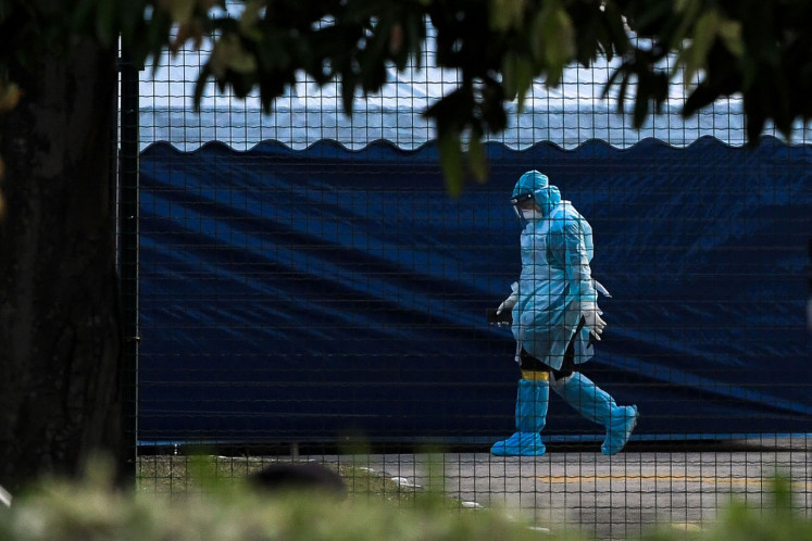 A National Disaster Management Agency (NADMA) officer wearing a hazardous materials suit walks through a health screening area of the Air Disaster Unit (ADA) at Kuala Lumpur International Airport (KLIA) in Sepang, Malaysia, on Tuesday, Feb. 4, 2020. (Bloomberg/Samsul Said)