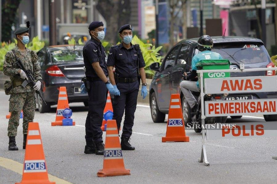 Police officers and Armed Forces personnel manning a roadblock at Jalan Ampang this morning. - NSTP/ASYRAF HAMZAH