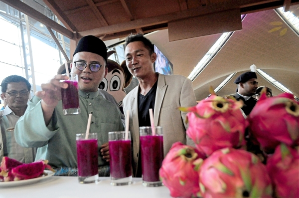 Amirudin (left) trying the dragon fruit juice at the launch of Visit Sepang Year 2020 as orchard owner Lee Chee Wei looks on.