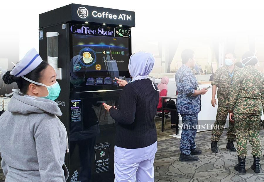 Frontliners at MAEPS enjoying coffee from Fauzan's coffee machine.