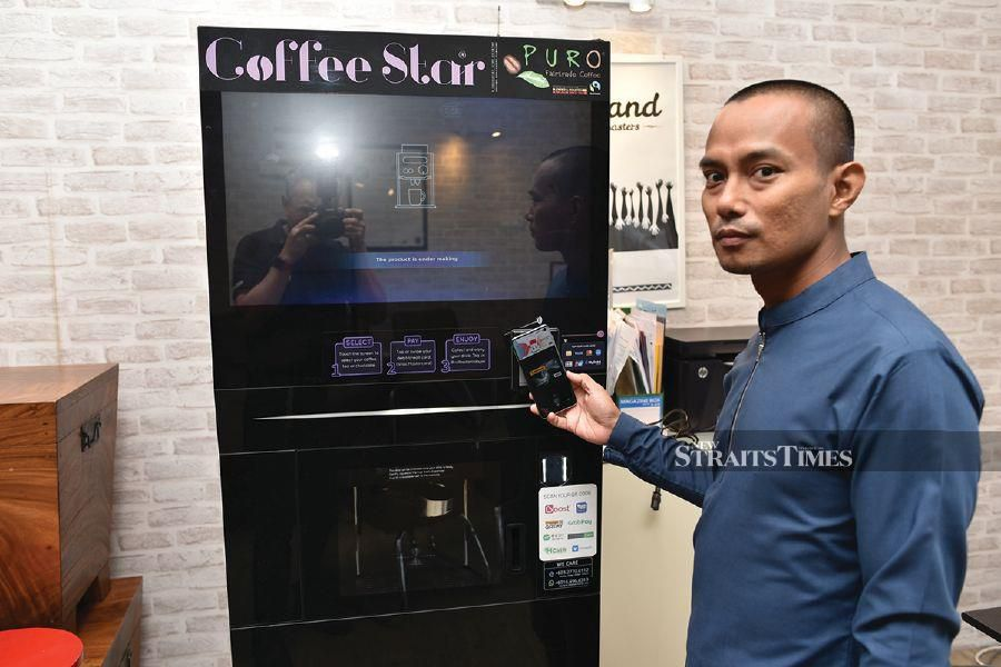Raja Ahmad Fauzan Raja Hassan showing how the cashless payment system of the Coffee ATM works.