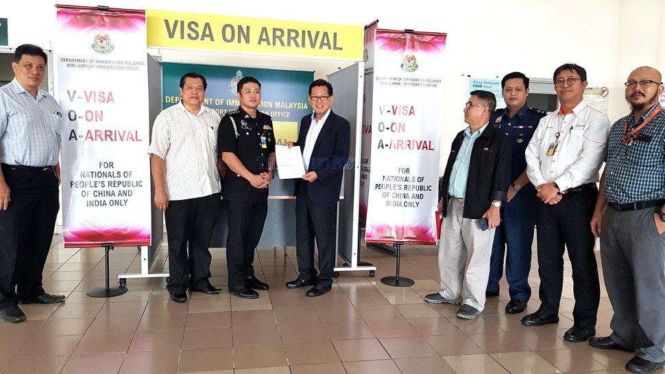 Assistant Minister of Tourism, Arts and Culture Datuk Lee Kim Shin holds a VoA form. From second left are Acting Miri Resident Abdul Aziz Mohamad Yusuf and Pellax